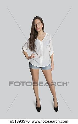 Portrait Of Confident Teenage Girl In Hot Pants Posing Over Gray Background