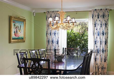 Chandelier over table and chairs in contemporary dining room; West Palm  Beach; USA Stock Photo