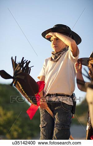 Dos Niños Vestido Como Vaqueros En Pasatiempo Caballos