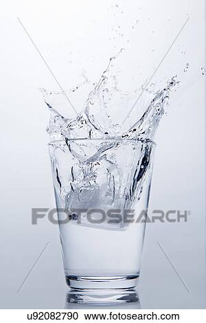 Stock Photography Of Ice Cube Splashing Into Glass Of Clear Water