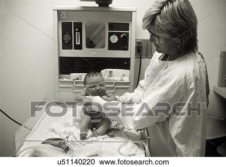 Female nurse cleaning, tagging and checking newborn baby in