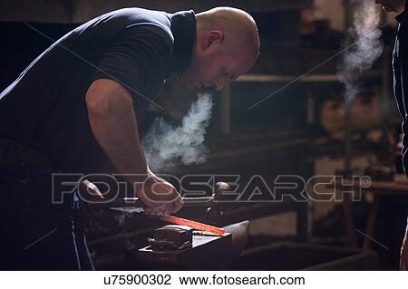 Farrier forging horseshoe on anvil Stock Image