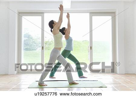 two young women practicing yoga standing and stretching