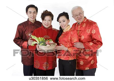 stock images of family in traditional clothes holding food to celebrating chinese new year and. Black Bedroom Furniture Sets. Home Design Ideas