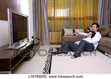 Couple Sitting On Floor Leaning On Sofa Watching TV