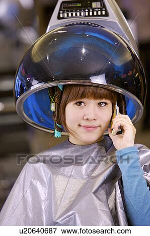 Young Woman Sitting Under Hair Dryer And Holding Mobile