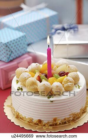 Birthday Cake With A Lighted Candle On Top Wrapped Presents In The Background