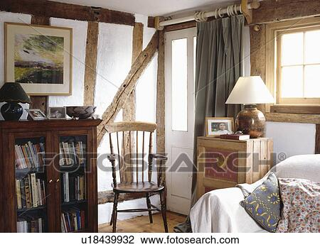 antieke boekenkast en houten stoel in huisje livingroom met blootgestelde muur balken