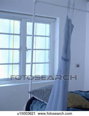 stock fotografie blaues kleid h ngender wei metall bett vor fenster in wei. Black Bedroom Furniture Sets. Home Design Ideas