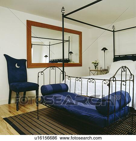 Blue Striped Cushions On Metal Daybed Below Modern Black Iron Four Poster Bed In White Bedroom With Chair