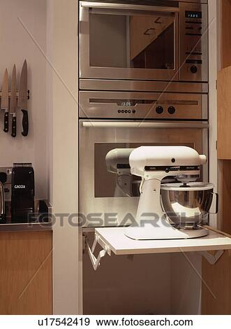 Close Up Of White Kitchenaid Mixer On Retractable Shelf In Front Of Double Stainless Steel Oven Stock Photo