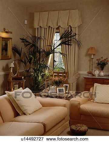 Cream curtains and sofas in traditional living room Stock ...
