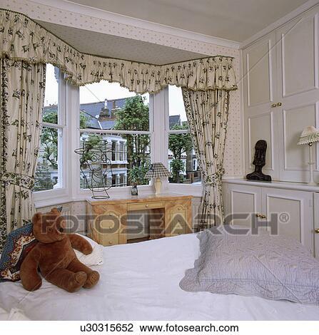 Creamgreen Kwiatowy Firanki Na Wykusz W Tradycyjny Biały Sypialnia Z Teddybear Na łóżku Z Biały Płótno Bank Zdjęć