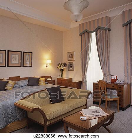 Crema, divano, in, camera letto hotel, con, strisce, tenda, e, biancheria  da letto Archivio fotografico