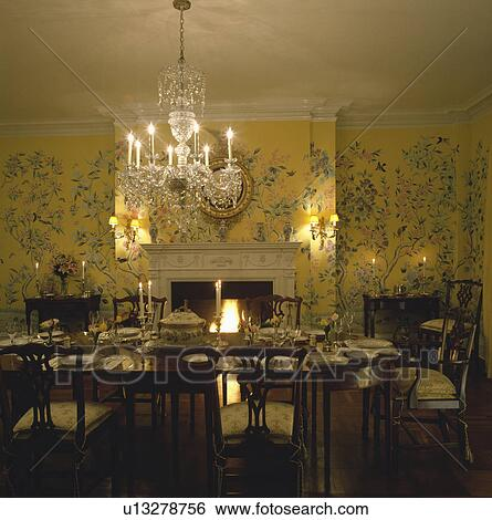 Crystal Chandelier Above Place Settings On Table In Georgian Dining Room With Floral Patterned Yellow Wallpaper