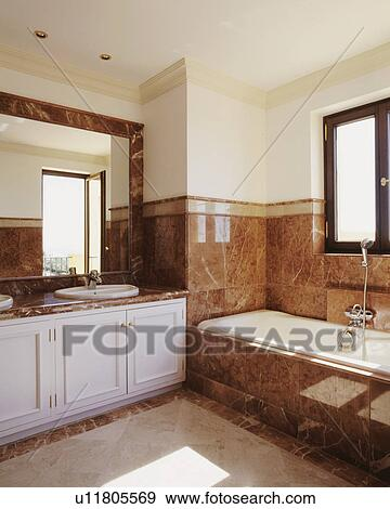 Stock Photograph Of Earth Coloured Marble Tiles Above Bath And On
