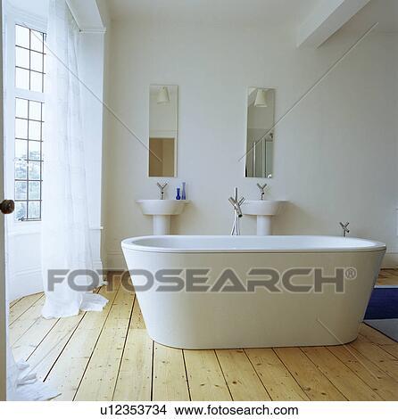 Freestanding White Bath In Middle Of Bathroom On Pine Floor