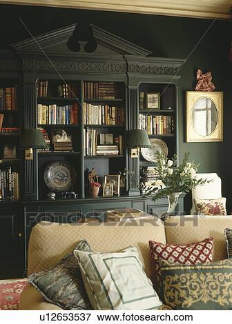 Gepaßt, bücherregale, mit, giebeldreieck, in, dunkles grün, wohnzimmer,  mit, kissen, angehäuft, auf, creme, sofa Stock Foto