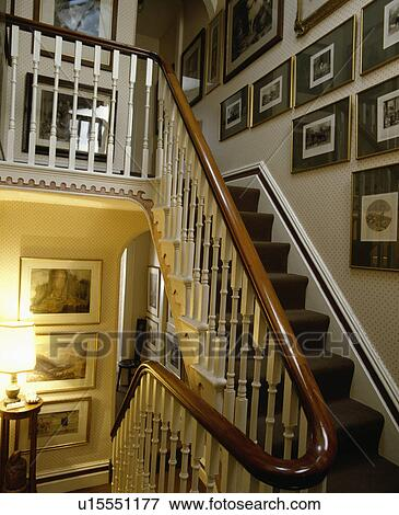Group Of Pictures On Wall Above Victorian Staircase With White Bannisters  And Mahogany Handrail