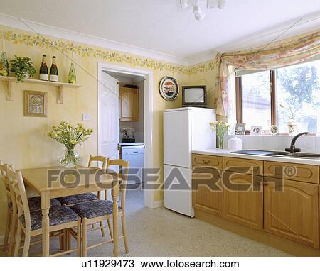 Klein, fernsehen, oben, kühlschrank tiefkühlschrank, in, pastell, gelb,  kueche, esszimmer, mit, gepaßt, einheiten, und, holztisch Stock Bild