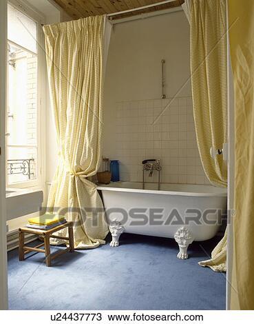 lang gele gordijnen getrokken back om te onthullen witte clawfoot bad in traditionele badkamer met blauwe tapijt