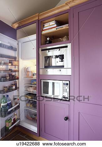 Large Fridge Freezer With Open Door Beside Microwave And Oven Built Into Purple Kitchen Cupboard