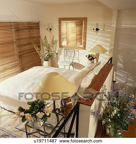 Mezzanine Bedroom With Slatted Wooden Blinds At Window And Cream Lamps On  Tables On Either Side Of Bed