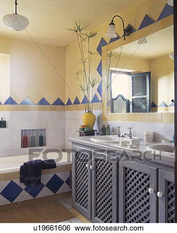 Mirror Above Pale Grey Vanity Unit In Pastel Yellow Mediterranean Bathroom With Blue White Tiled Edging On Bath