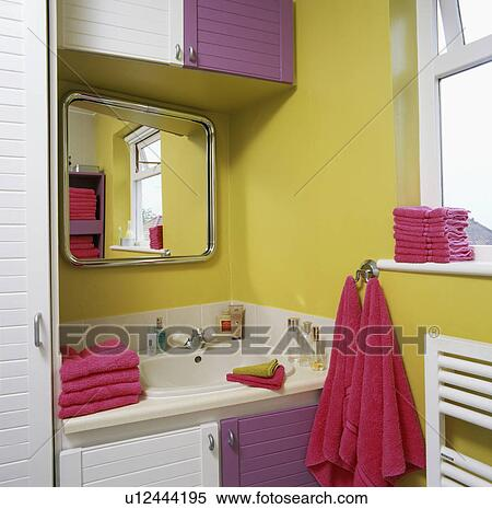Mirror Above White Built In Sink Yellow Bathroom Wit Pink Towels And Purple Doors On The Cupboards