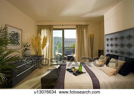 Neutre, chambre à coucher, à, noir, meubles, et, crème, rideaux, à, portes  patio, dans, moderne, espagnol, appartement Image