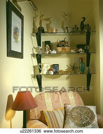 Ornaments on glass shelves above armchair in corner of ...