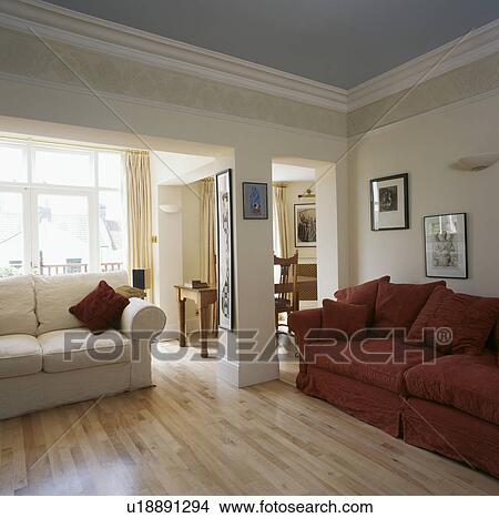 Red And Cream Sofas In Cream Living Room With Laminated Wood