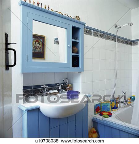 Reflété, mur bleu, cabinet, au-dessus, bassin, construit, dans, bleu, bois,  vanité, unité, dans, blanc, carrelé, salle bains Banque de Photo