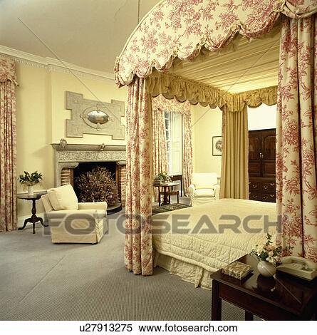 roze toile de jouy drapes en room stikken op fourposter bed in groot pastel gele land slaapkamer met grijze tapijt