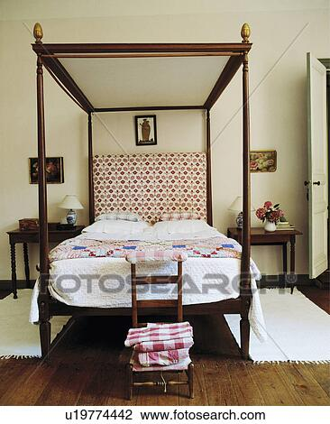 Simple Four Poster Bed With White Quilt And Patchwork In Country Bedroom Rugs On Wooden Floor
