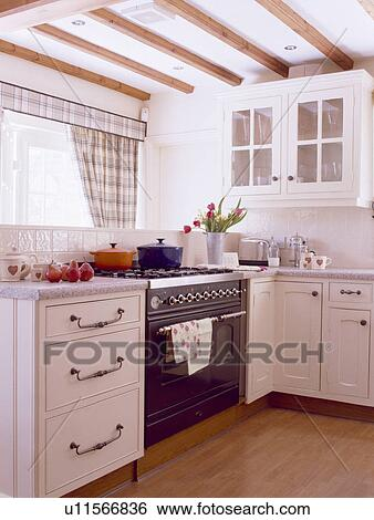 Small White Country Kitchen With Wooden Flooring And Black Oven