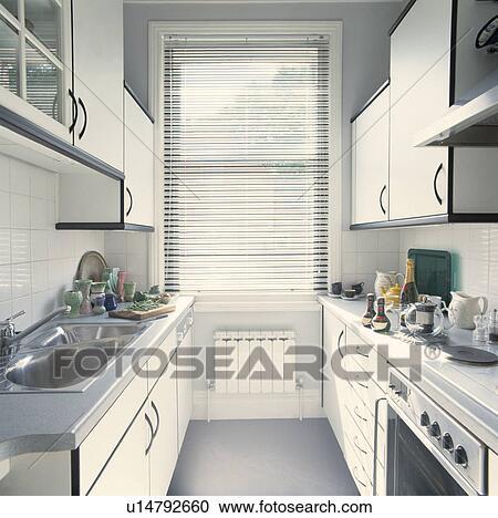 Smalle Keuken Met Witte Gepaste Kasten Stock Afbeelding