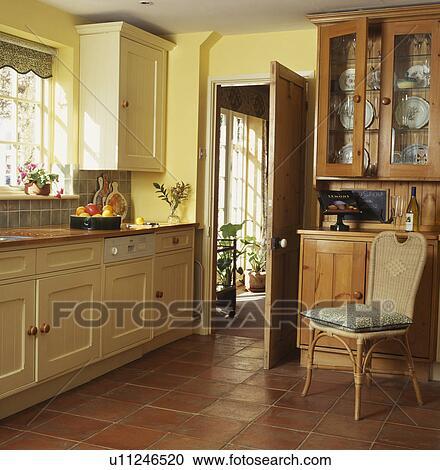 Terracotta Fussbodenfliesen In Gelb Landhauskuche Mit Kruckstock Stuhl Vor Kiefer Kommode Stock Bild