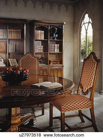 Upholstered Gothic-style chairs in country dining room with large bookcase  Stock Photo