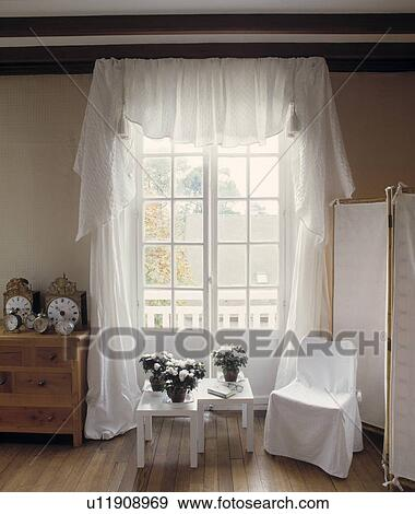 White Loosecover On Chair In Front Of French Windows With