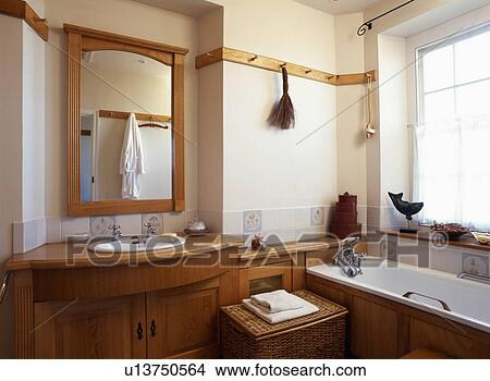 Wooden Framed Mirror Above Basin Built Into Wooden Vanity Unit And Pegrail On Wall Above Bath Picture U13750564 Fotosearch