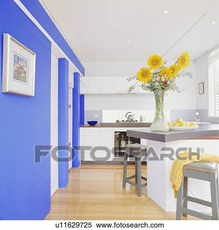 Yellow Sunflowers In Tall Glass Vase On Worktop In Modern White Kitchen With Wooden Flooring And Bright Blue Wall Stock Photography U11629725 Fotosearch