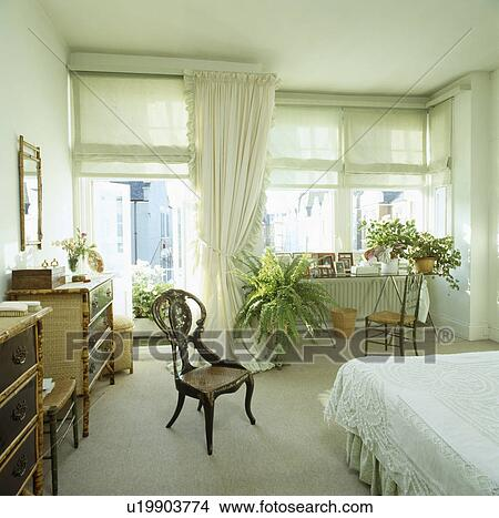 Antique inlaid chair and cream carpet in white bedroom with green blinds  and white curtains on the windows Picture
