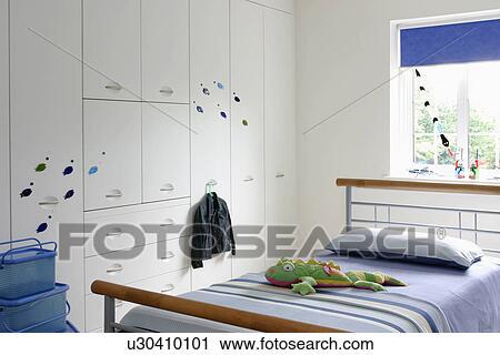 Blauwe Gestreepte Dekking Op Hout En Metaal Bed In Kind Hippe Witte Slaapkamer Met Witte Gepaste Opslag Kast Stock Afbeelding
