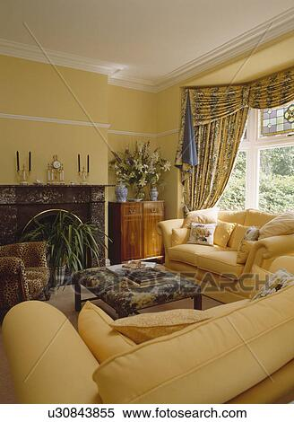 Blue And Yellow Swagged Curtains In Pastel Living Room With Pale Sofas