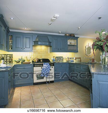 Blue Cupboards In Modern Yellow Kitchen With White Oven And Limestone Floor Tiles Stock Photograph U16656716 Fotosearch