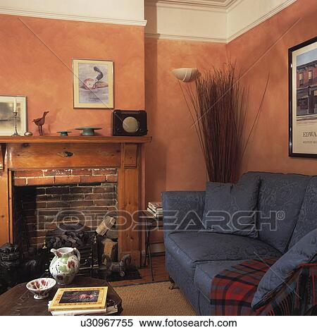 Blue Sofa In Terracotta Living Room With Pine Fireplace Stock Photography