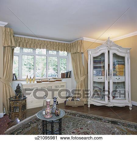 creme soie rideaux et glass fronted blanc peint placard dans chambre a coucher a marocain cruches et tables banque d image
