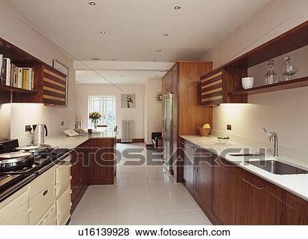 Cream Aga In Modern Kitchen With Walnut Fitted Cupboards And White Floor Tiles And Worktops Stock Photo U16139928 Fotosearch