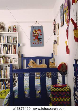 Fabric Wall Hanging Above Blue Wooden Bed In Childu0027s Bedroom With White  Bookshelves